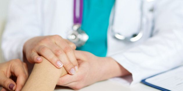 Female doctor's hands holding patient's hand for encouragement and empathy. Partnership, trust and medical ethics concept. Bad news lessening and support.