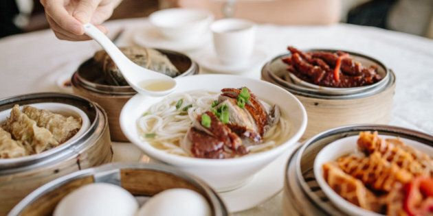 Enjoying noodles and variety of dim sum in Chinese restaurant.