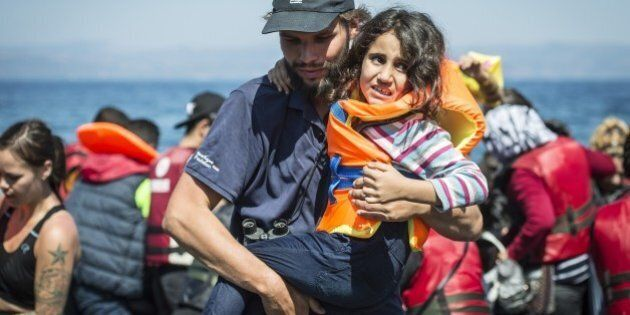 LESBOS ISLAND, GREECE - SEPTEMBER 19: A volunteer carries a refugee girl upon her arrival on the shore of Eftalou beach, north of the port city of Mytilini after crossing the Aegean sea from Turkey on September 19, 2015 in Lesbos Island, Greece. (Photo by Ozge Elif Kizil/Anadolu Agency/Getty Images)