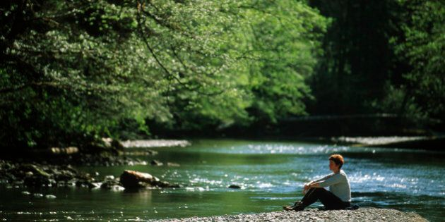 Woman sitting on gravel bar with a river flowing by, Carmanah Walbran Provincial Park, Vancouver Island,...