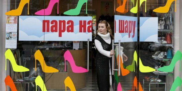 A woman leaves a shoe store in central Kiev, Ukraine, April 25, 2016. An inscription