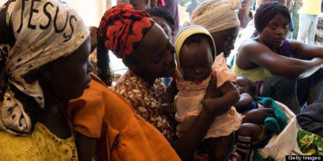 Mother with their babies queue to get a health check at Rwamwanja refugee camp, in the Kamwenge district,...