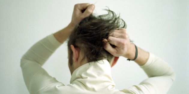 Backview of man pulling his hair