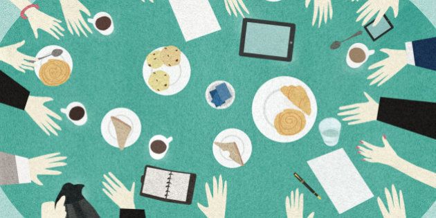 Directly above view of business people meeting around table with breakfast