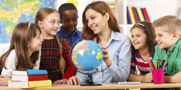 Teacher and children looking at globe