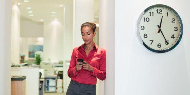 Businesswoman in office using PDA near a clock