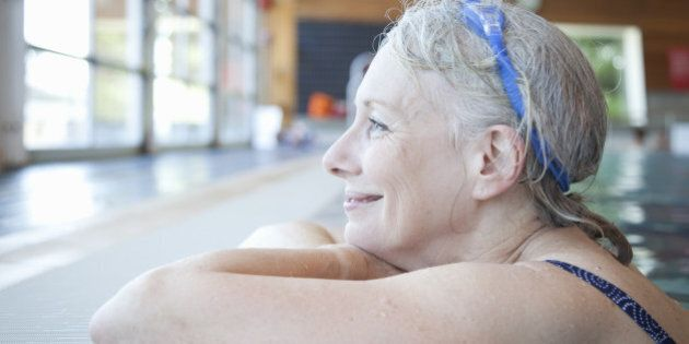 Senior baby boomer woman resting on edge of swimming pool, enjoying a quite moment