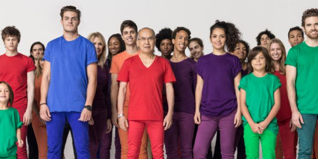 Studio shot of a mixed age, multiethnic large group of smiling men and women, wearing monochromatic colors