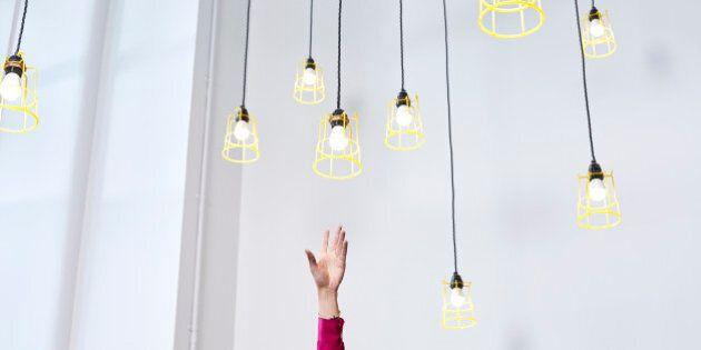 A hand reaching for conceptual idea lightbulbs