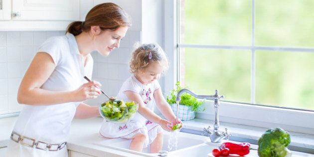 Young beautiful mother and her cute curly toddler daughter washing vegetables together in a kitchen sink...