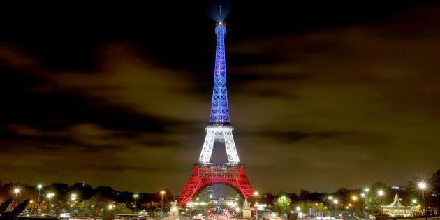 PARIS, FRANCE - NOVEMBER 16: The Eiffel Tower is illuminated in Red, White and Blue in honour of the...