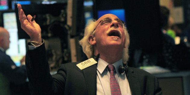 Traders react at the end of trade at the New York Stock Exchange in New York, March 5, 2013. The Dow...