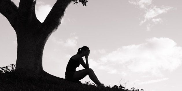 silhouette of sad woman sitting