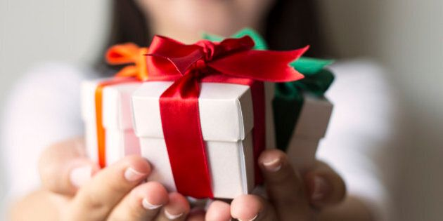 Woman holding a small gift box in a gesture of giving. Christmas holiday or special occasion gift box with red, green and orange ribbon.