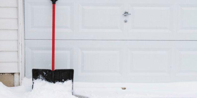 snow shovel leaning up on garage door.