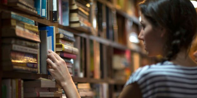 Beautiful woman looking at books in a library. Ambient light to emphasize the mood and location. Converted from RAW.