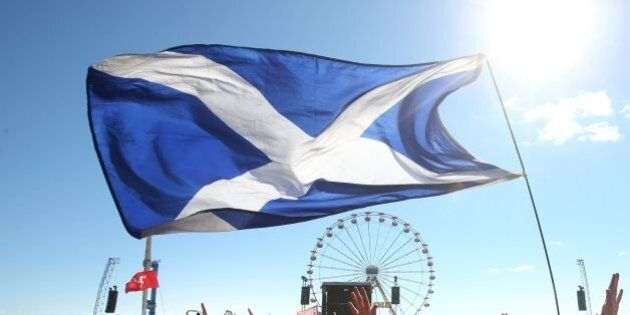 Music fans with a Saltire Flag in front of the Main Stage at the T in the Park music festival held at...