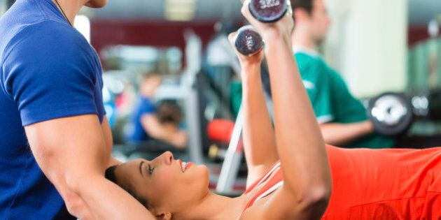 Woman with her personal fitness trainer in the gym exercising with