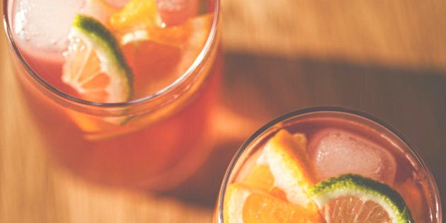 Top down view of 2 glasses of fruity punch with ice cubes and slices of lime and orange.