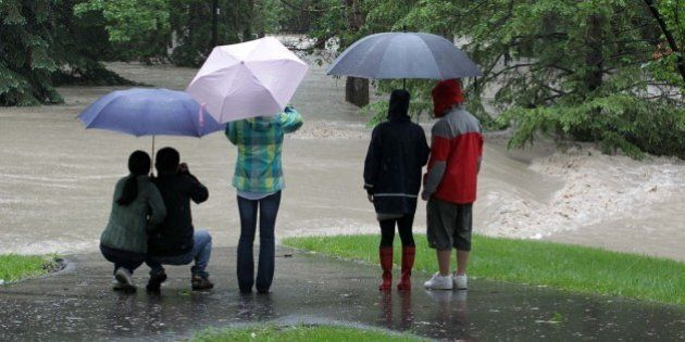 A once peaceful park path disappears into a flooded torrent as waters rise in Calgary, Alberta, Canada,...