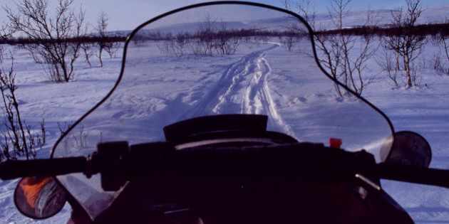 Sweden, Lapland, Arctic Circle. View over the front of a snowmobile on a trail through