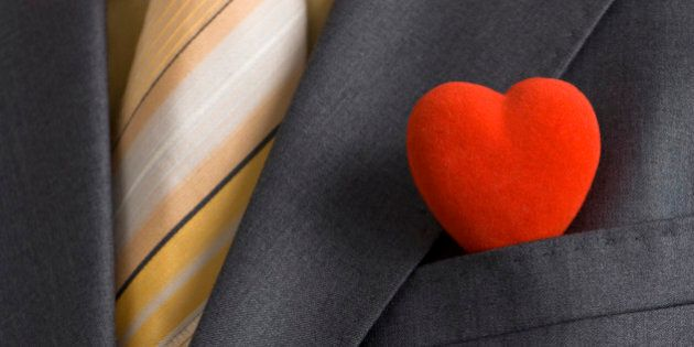 A red heart in a suit pocket representing the business card of modern Mr.