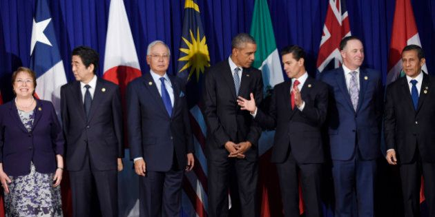 President Barack Obama talks with Mexico's President Enrique Pena Nieto as other leaders of the Trans-Pacific...