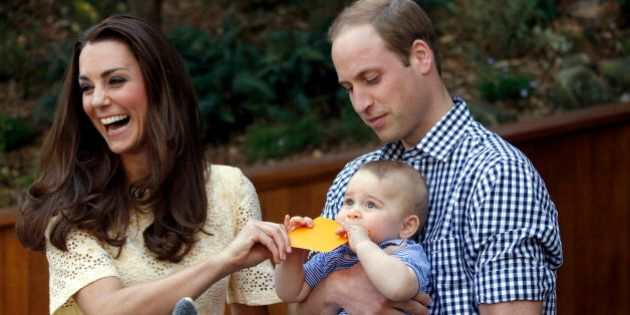 Britain's Kate, the Duchess of Cambridge, and her husband Prince William react as their son Prince George bites a small present that was given to him during a visit to Sydney's Taronga Zoo, Australia Sunday, April 20, 2014.  (AP Photo/David Gray, Pool)