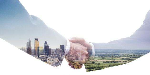 A double exposure of two business men shaking hands with a view of the City of London and of a green...