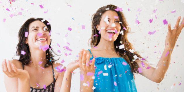 Hispanic women throwing confetti at party