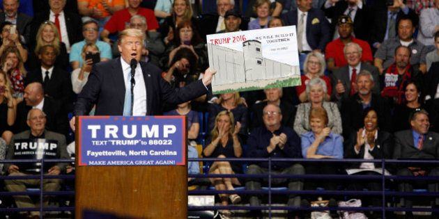 U.S. Republican presidential candidate Donald Trump holds a sign supporting his plan to build a wall between the United States and Mexico that he borrowed from a member of the audience at his campaign rally in Fayetteville, North Carolina March 9, 2016. Trump was interrupted repeatedly by demonstrators during his rally.    REUTERS/Jonathan Drake