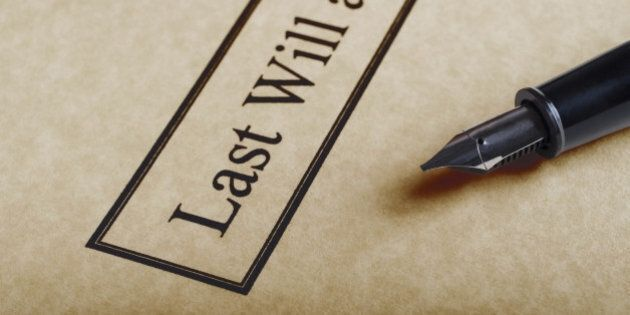 Close up of the bordered title of a last Will and Testament set on parchment paper with nib of fountain...