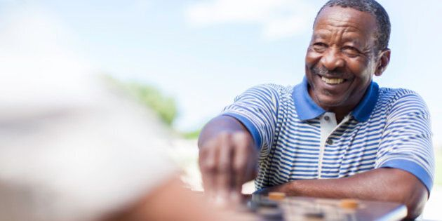African male senior smiling, playing a game of chess against his friend in Langebaan, Western Cape, South