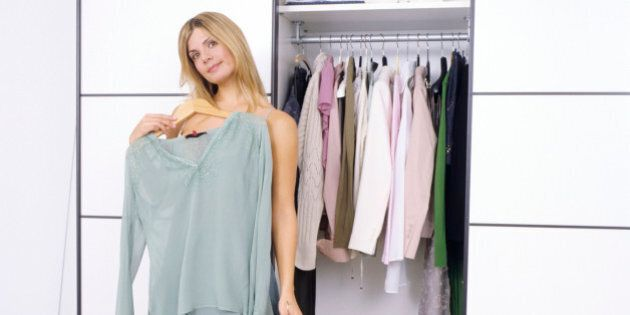young woman in front of wardrobe trying on green blouse