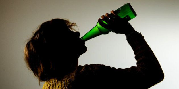 PICTURE POSED BY MODEL A woman drinking alcohol.