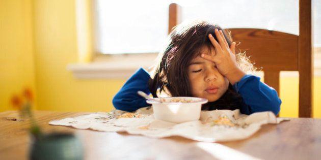 Tired toddler girl sitting at breakfast