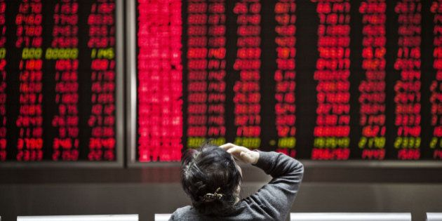 A woman sits in front of electronic boards displaying stock information at a securities brokerage in...
