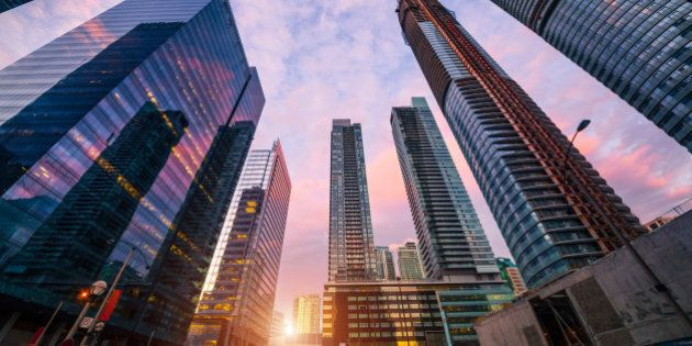 Low angle view of compact modern skyscrapers in busy Toronto downtown district during sunset.