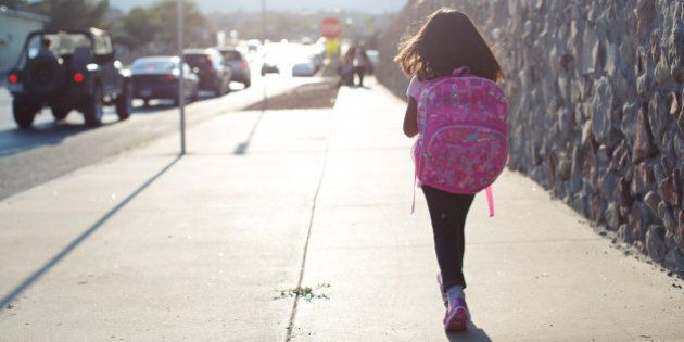 A young girl walks to school along a busy street wearing her backpack.