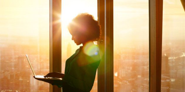 Businesswoman on laptop at window in morning