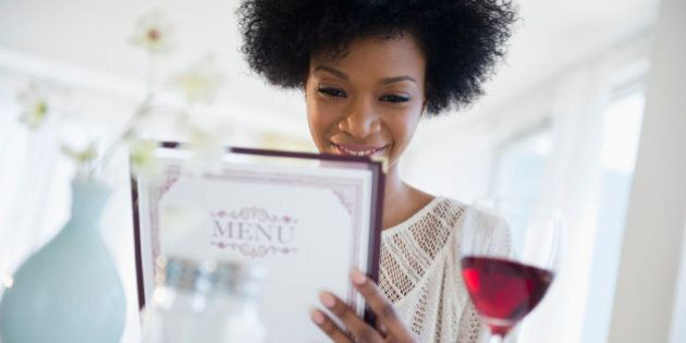 African American people reading menu at restaurant
