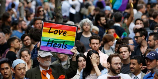 A man walks through the crowd holding a sign during a vigil and memorial for victims of the Orlando nightclub...