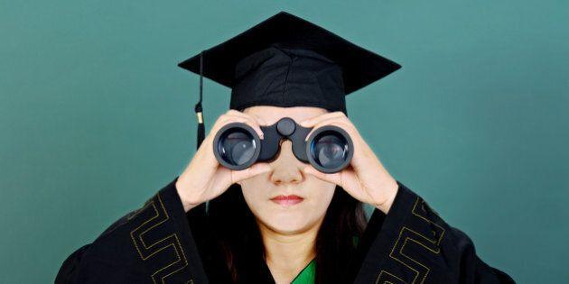 Female graduate looking through binoculars against green