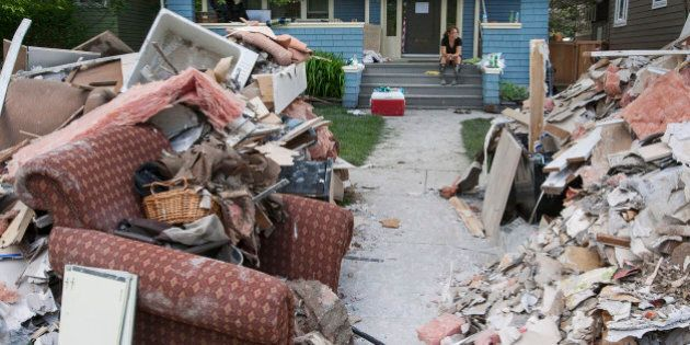 Laura Colpitts sits on the front porch of her Elbow Park home as debris and damaged belongings sit in...