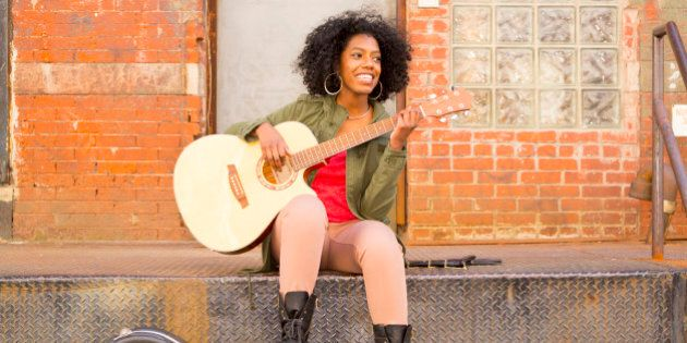 Mixed race woman playing guitar in