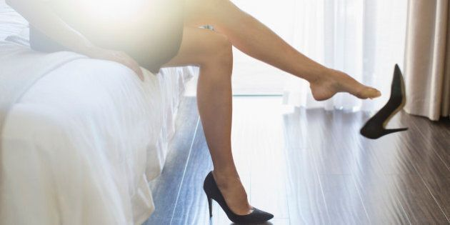 Businesswoman kicking off her shoes in hotel