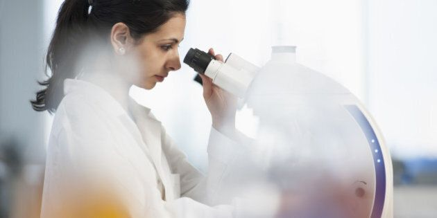 Pakistani scientist using microscope in