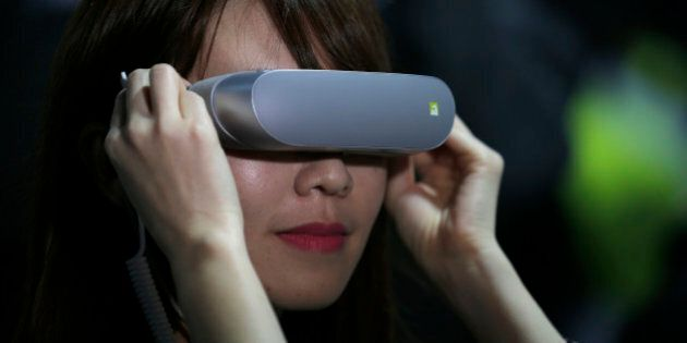 A woman uses the LG 360 VR glasses during the LG unpacked 2016 event on the eve of this weeks Mobile World Congress wireless show, in Barcelona, Spain, Sunday, Feb. 21. 2016. (AP Photo/Manu Fernandez)