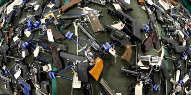 "FILE PHOTO:  Guns are displayed at the Rocky Mountain Gun Show in Sandy, Utah, U.S. on Saturday, Jan. 7, 2012. The National Rifle Association called for stationing police officers in schools as the proper response to the Dec. 14, 2012 school shooting in Connecticut and blamed ""blood-soaked films"" and video games for the violence. Photographer: George Frey/Bloomberg via Getty Images"