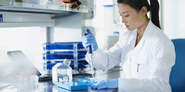 Scientist pipetting samples into eppendorf tubes in research